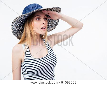 Young woman in hat looking into distance over white background
