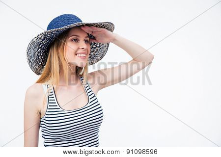 Happy cute woman in hat looking into distance over white background