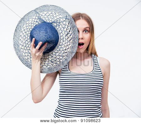 Surprised woman covering her eye with hat over gray background. Looking at camera