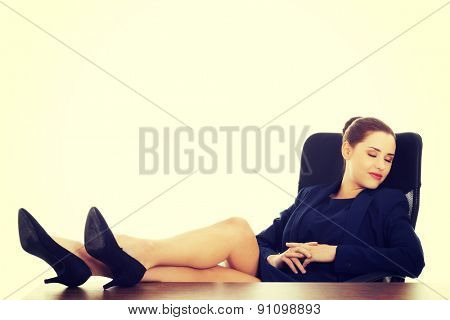 Relaxed young businesswoman sitting with legs on desk