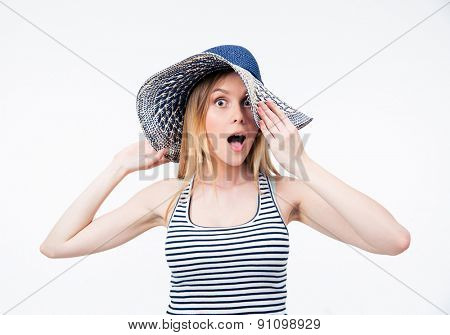 Portrait of a surprised woman in hat looking at camera over gray background