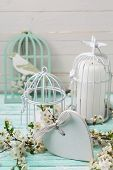stock photo of caged  - Background with flowering branches of trees decorative heart and candles in bird cages on turquoise painted wooden planks - JPG