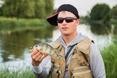 stock photo of fisherman  - Young fisherman on the river bank - JPG