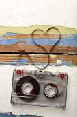 stock photo of magnetic tape  - Audio cassette with magnetic tape in shape of heart on wooden background - JPG
