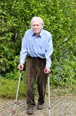 stock photo of cobblestone  - Elderly man with casual clothes using forearm crutches as a mobility aid to walk on the cobblestones of a footpath in a green park or yard full length - JPG