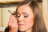 pic of makeup artist  - Makeup artist paints the eyebrows model - JPG