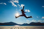 picture of dock a lake  - Girl jumping in the sun on the dock of a lake - JPG