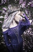 foto of magnolia  - Beautiful young woman standing in front of blooming magnolia tree wearing medieval purple gown and crown made out of twigs - JPG