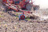 foto of cultivator-harrow  - The tractor harrowing the large brown field in spring season - JPG