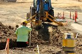 picture of excavator  - Construction excavation contractor uses a level rod and laser to dig a trench for a concrete fondation wall