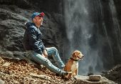 pic of waterfalls  - Man With Dog Sitting Near Waterfall  - JPG