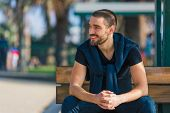 picture of sitting a bench  - Handsome smiling and casual young man sitting on bench - JPG