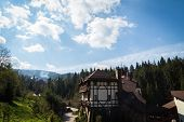 stock photo of twisty  - Mountain town house on a hill below the house a small mountain stream - JPG