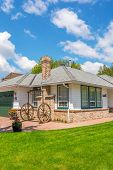 picture of wagon wheel  - Cozy house with wagon wheel decoration - JPG