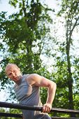 picture of vest  - Young man in grey vest having outdoor workout - JPG