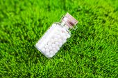 foto of placebo  - homeopathic pills on a natural grass background - JPG