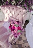 stock photo of purple rose  - a silk purple chair lies a bouquet of lilacs and roses  - JPG