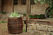 picture of flower pot  - in the courtyard of a stone house on the porch with pots of flowers and a big barrel with flowers - JPG