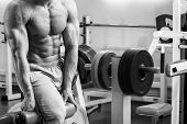 stock photo of abdominal muscle man  - A man pumping abdominal muscles in the gym - JPG