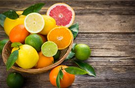 picture of fruits  - Fresh and juicy citrus fruits in the basket on the rustic table - JPG