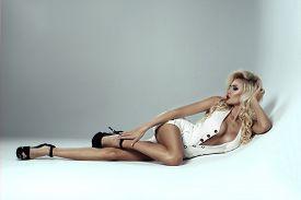 stock photo of big lips  - Sexy model with big breast lying on white floor - JPG