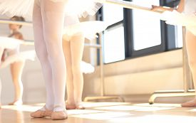 stock photo of  dancer  - Young ballerinas wearing pointe shoes the special reinforced satin shoes allowing a ballet dancer to stand on tip toe low angle view of a class in progress - JPG
