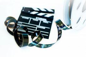 image of mm  - Movie clapper and vintage 35 mm film cinema reel on white background filmstrip selective focus  - JPG