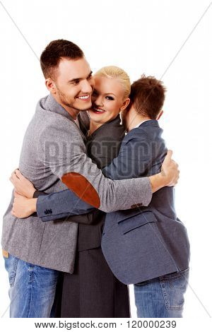 Happy group of three people hugging