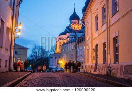 People Walk Down The Street Of Old Tallinn