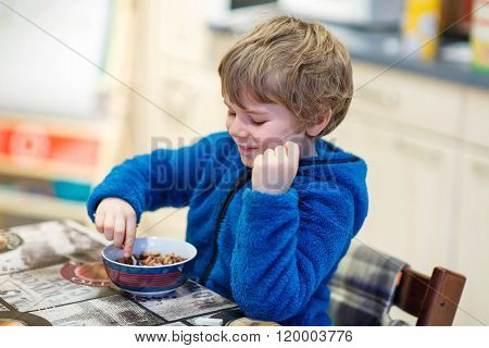 Little kid boy eating cereals for breakfast