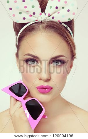 Vintage style portrait of young beautiful sexy girl with fancy hairband and hot pink sunglasses in her hand