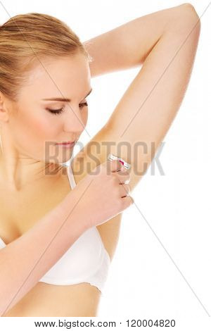 Young woman shaving armpit pink razor