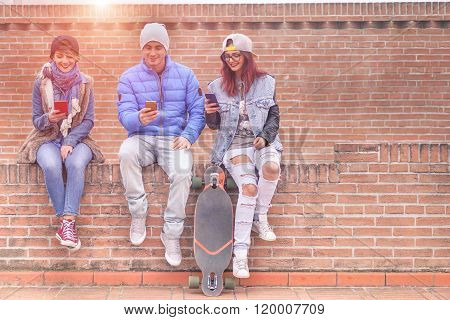 Group Of Young Friends Playing Online With Smartphones Outdoor
