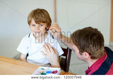 Dad painting flag on face of little kid for football or soccer
