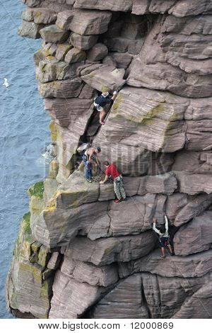 Climbers ascending the 'Old Man of Stoer'