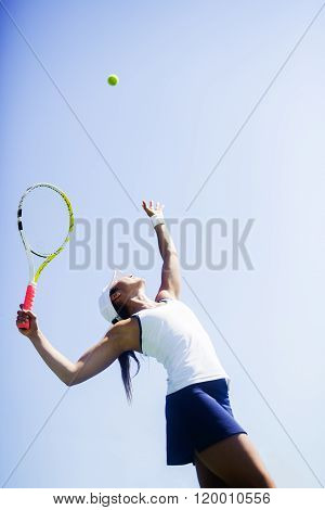 Beautiful young female tennis player serving outdoor