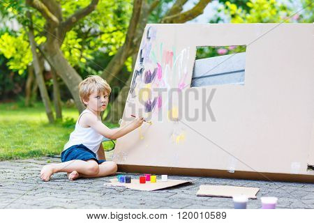Little kid boy painting big paper house with colorful paintbox