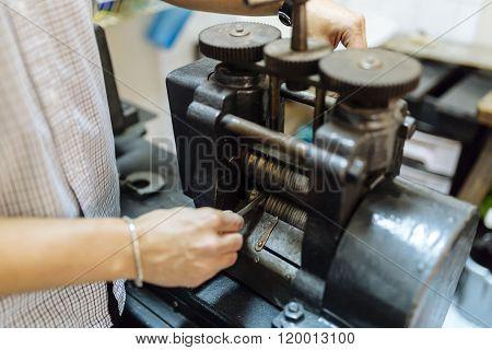 Goldsmith using machine to make metal thinner