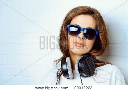 Modern young woman listening to music on headphones standing by a brick wall. Youth style.