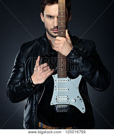Handsome man holding the guitar