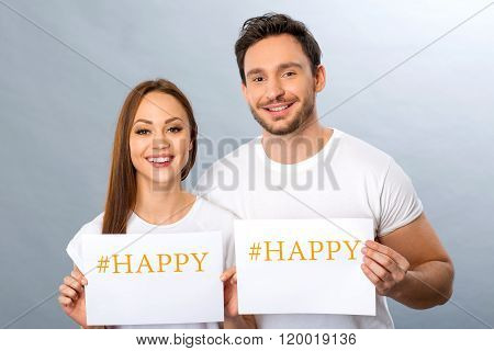 Cheerful young couple holding shits of paper