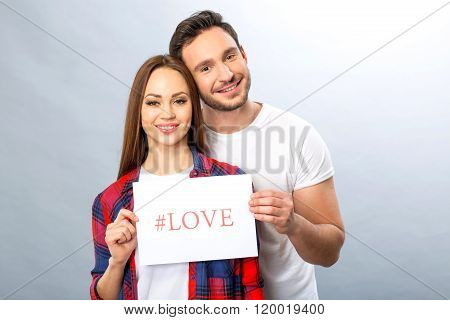 Nice young couple holding shit of paper