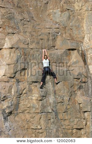 Female climber ascending sheer cliff face
