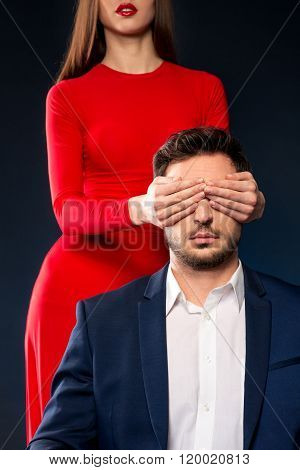Attractive woman closing eyes of handsome man