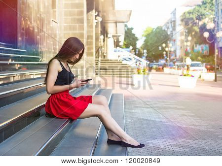 Young happy caucasian woman texting sms in city outdoor. Relax lifestyle summer concept