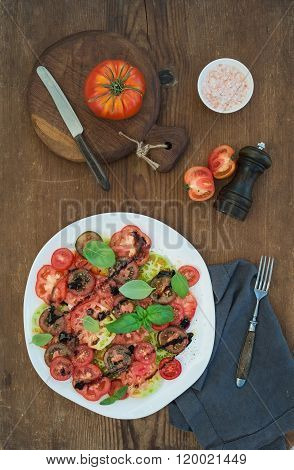 Ripe village heirloom tomato salad with olive oil, basil and spices over rustic wooden background