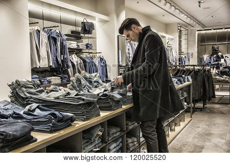 Young man choosing shirt