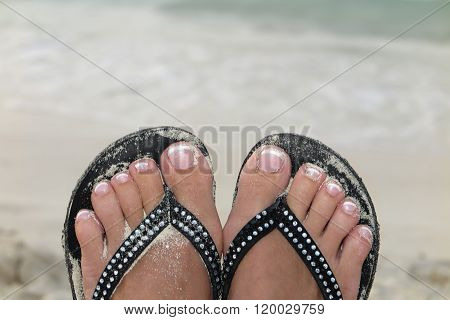 Woman Feet With White Toenails On Natural Beach Sand