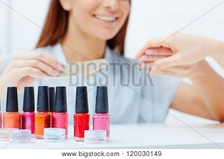 Row of multi-color nail lacquers in beauty salon on background of manicurist