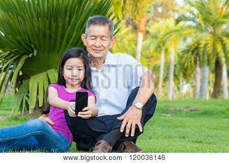 Asian Grandfather And Grandchild Taking Selfie With Smartphone